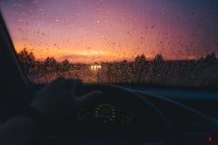 下雨在汽车玻璃背景的下落与红色日落 免版税库存图片