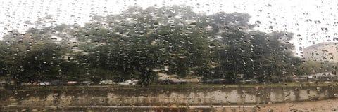 下雨在湿窗口和街道树、蓝天和风雨如磐的雨云的下落后边,被弄脏的城市bokeh 多雨天气, se的概念 免版税库存图片