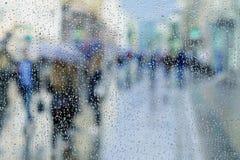下雨在湿窗口,被弄脏的人民,城市轻的bokeh的下落 多雨天气,季节,现代城市的概念 复制空间 库存图片