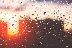 下雨在玻璃窗的下落以日落为背景 库存照片