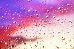 下雨在玻璃窗的下落以明亮为背景 免版税库存照片