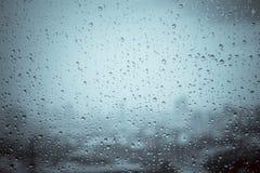 下雨在玻璃窗的下落在纹理w之外背景水  库存图片