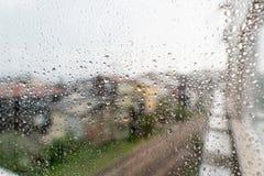 下雨在玻璃窗的下落浮出水面有城市背景 在都市背景隔绝的雨珠的自然样式 免版税库存照片