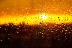 下雨在玻璃窗的下落纹理与华美的五颜六色的橙色琥珀色的日落光摘要 免版税库存图片