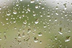 下雨在窗口与大厦和绿色树的下落在背景 库存照片