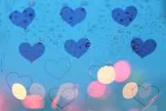 下雨在窗口的下落与在心脏框架背景的轻的bokeh 免版税库存图片