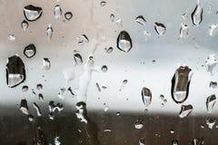 下雨在窗口的下落与在背景的一个城市大厦 库存图片