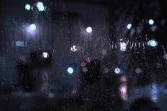 下雨在窗口的下落与街道bokeh光 免版税库存照片