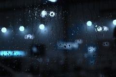 下雨在窗口的下落与街道bokeh光 免版税库存图片