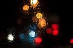 下雨在窗口的下落与路光bokeh 免版税库存照片