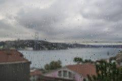 下雨在窗口的下落反对伊斯坦布尔,土耳其城市视图  免版税库存照片