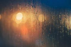 下雨在窗口的下落反对bokeh光 免版税库存图片