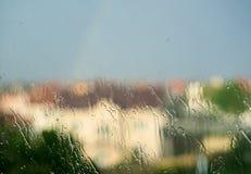 下雨在窗口的下落在与房子的雨期间背景的 免版税库存照片