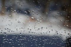 下雨在窗口的下落有森林和雪背景 免版税库存图片