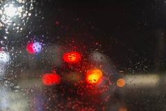 下雨在窗口,多雨天气,雨背景的下落 模糊的汽车剪影 雨天,夜 图库摄影