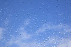 下雨在窗玻璃和蓝天的下落 免版税库存照片