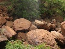 下雨在红色岩石的瀑布 免版税库存图片