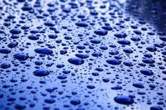 下雨在蓝色车身,浅焦点的下落 免版税图库摄影