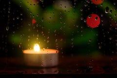 下雨在镜子的下落有蜡烛光的被弄脏的图象的 免版税库存照片