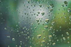 下雨在镜子的下落有绿色自然光的 库存图片
