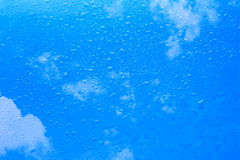 下雨在玻璃的下落与蓝天云彩 库存图片