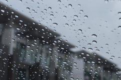 下雨在玻璃看法的下落从在房子背景的汽车 免版税库存照片