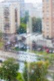 下雨在玻璃窗和被弄脏的街道的下落 库存图片