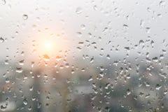 下雨在玻璃窗的下落和被弄脏的都市风景和阳光  免版税库存图片