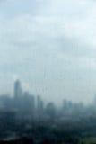 下雨在玻璃窗的下落和被弄脏的都市风景和阳光  库存图片