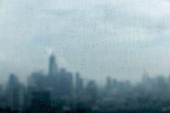下雨在玻璃窗的下落和被弄脏的都市风景和阳光  免版税库存照片