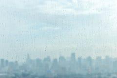 下雨在玻璃窗的下落和被弄脏的都市风景和阳光  库存照片