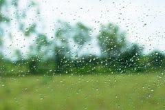 下雨玻璃表面和室外背景上的下落 免版税库存照片