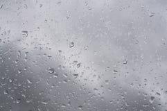 下雨玻璃表面上的waterdrops反对灰色天空 库存图片