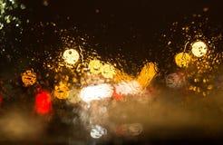 下雪与在汽车玻璃的小滴在晚上 免版税图库摄影