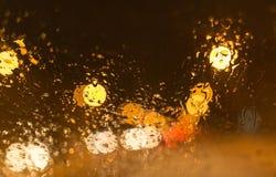 下雪与在汽车玻璃的小滴在晚上 免版税库存照片