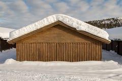 下雪在一个棕色大厦的屋顶,在蓝天的白色云彩 库存照片