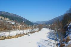 下雪在一条冻河在山村在早期的春天 库存图片
