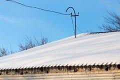 下雪在房子的屋顶在日落 免版税库存图片