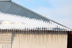 下雪在房子的屋顶在日落 库存图片