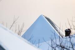 下雪在房子的屋顶在日落 图库摄影