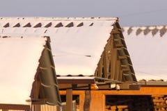 下雪在房子的屋顶在日落 库存照片