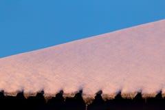下雪在房子的屋顶在日落 免版税库存照片