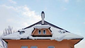 下雪在房子的屋顶在温暖 库存图片