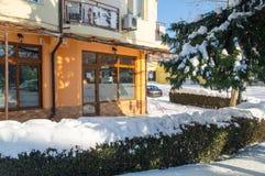 下雪在波摩莱老镇的街道上的绿色种植园在保加利亚,冬天 免版税库存照片