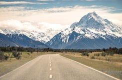 下雪的透视路山脉在多云天秋天海 免版税库存图片