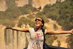从下面享用惊人的伊瓜苏瀑布的女孩。阿根廷边 免版税库存照片