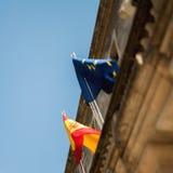 从下面被看见的西班牙旗子和欧盟旗子 免版税图库摄影