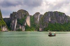 下龙湾与传统绿色渔船的岩层,联合国科教文组织世界自然遗产,越南 库存图片