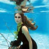 水下黑的礼服的年轻美丽的女孩 免版税库存照片