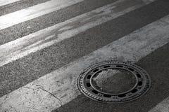 下水道在柏油路的人孔盖 库存图片